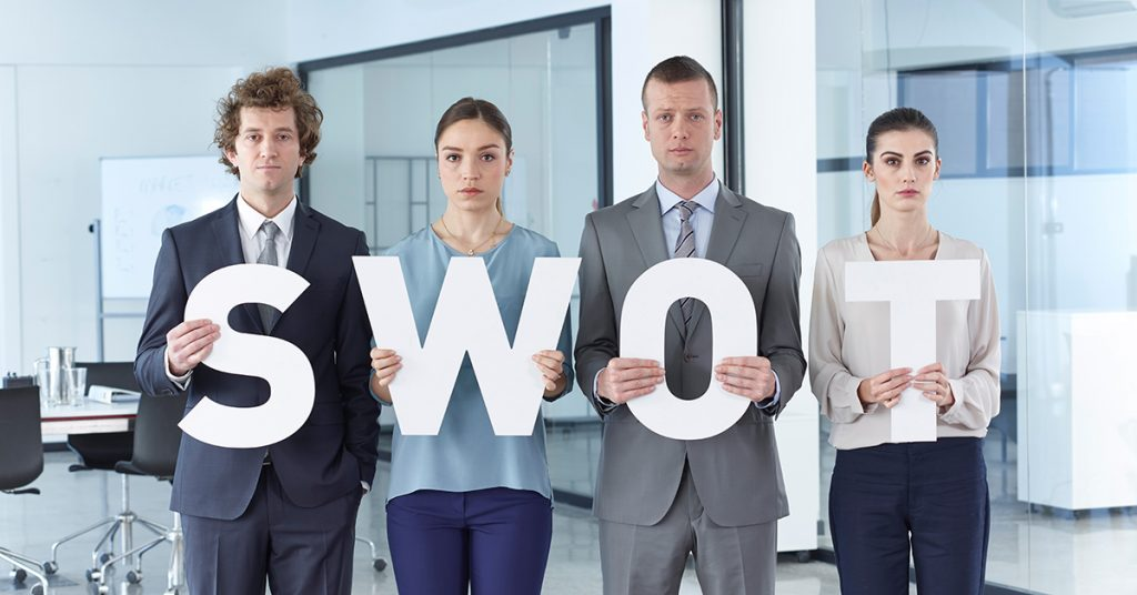 Team holding S.W.O.T. letters