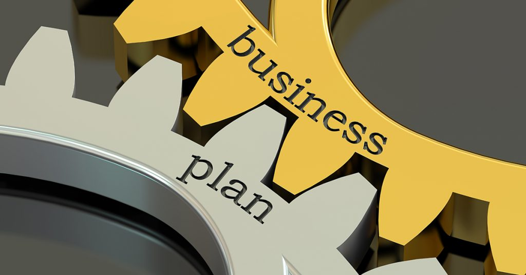 """Gear teeth meshing with words """"Business"""" and """"Plan"""""""