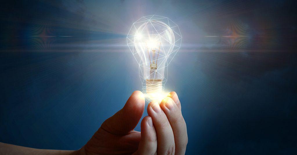 Hand holding glowing lightbulb